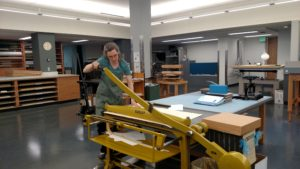 Kate Leonard, Lab Manager, demonstrates the cutting power of the board shear.