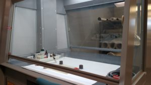 A fume hood stands ready to suck noxious fumes from adhesives.