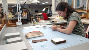 Intern Sarah Belasco meticulously repairs a small leather-bound book. A Kwikprint hot stamping machine stands in the background
