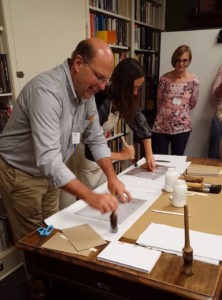 Todd Pattison and Amanda Nelsen, RBS Director of Programs & Education, go head-to-head in an in-class demonstration of case vs. adhered boards binding; student Ute Schechter and others observe.